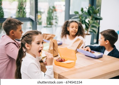 Multiethnic group of schoolkids eating lunch while sitting together at table