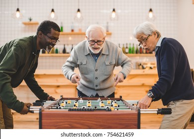 multiethnic group of senior friends playing kicker at bar