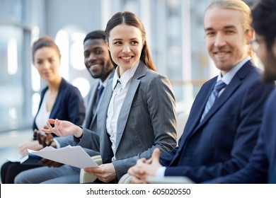 Multi-ethnic group of smiling business people sitting in row in modern glass hall, focus on young beautiful brunette woman