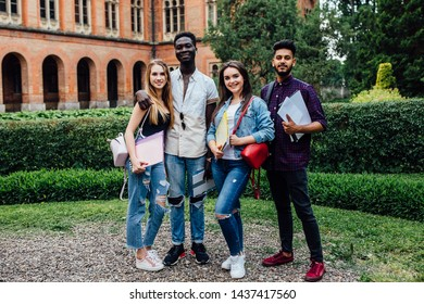 Multiethnic group of smiling students walking together walking near college and hugging.