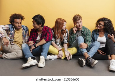 Multiethnic group of smiling young friends sitting and talking over yellow background