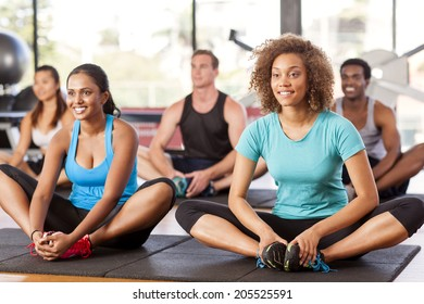 Multi-ethnic group stretching in a gym before their exercise class
