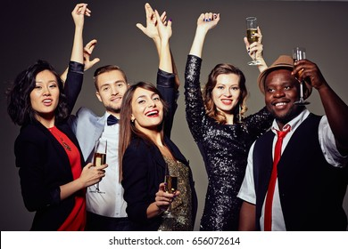 Multi-ethnic group of stylish friends dancing with hands up while celebrating momentous event in trendy night club, waist-up portrait