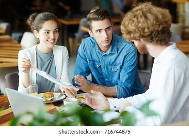 Multi-ethnic group of talented interior designers presenting ideas concerning joint project to their bearded client while having meeting at cozy restaurant