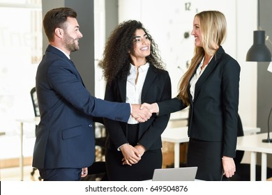 Multi-ethnic group of three businesspeople meeting in a modern office. Caucasian man and woman shaking hands wearing suit.