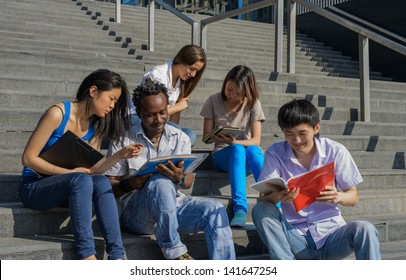 Multiethnic group of university students sitting on steps of university reading notes, metaphor for diversity and international friendship