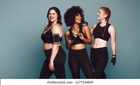 Multi-ethnic group of women together against grey background and smiling. Diverse group females in sportswear after workout.