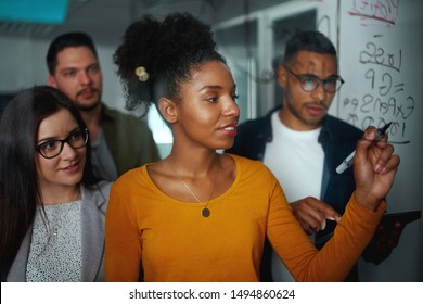Multi-ethnic group of young business people planning startup project on glass board in an office