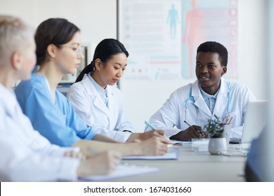 Multi-ethnic group of young doctors sitting round table during medical council or conference in clinic, copy space