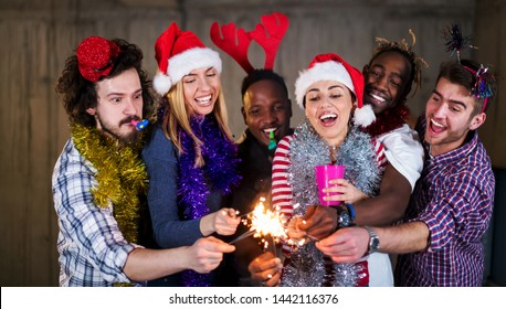 multiethnic group of young happy casual business people lighting a sparkler and having fun while celebrating new year eve in front of concrete wall at new startup office