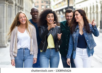 Multi-ethnic group of young people having fun together outdoors in urban background. group of people walking together pointing with the finger