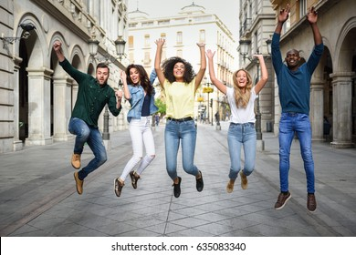 Multi-ethnic group of young people having fun together outdoors in urban background. group of people jumping together