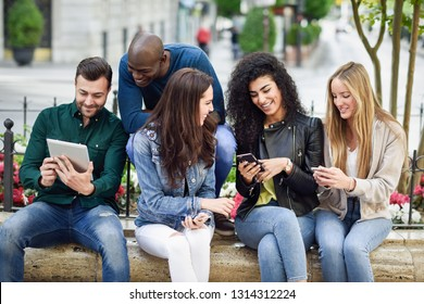Multi-ethnic group of young people using smartphone and tablet computers outdoors in urban background. Women and men smiling and laughing in the street wearing casual clothes.
