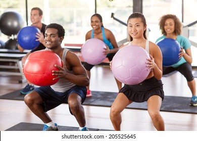 Multi-ethnic gym class doing squats with medicine balls