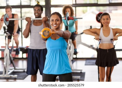 Multi-ethnic gym class doing various exercises