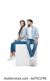 multiethnic happy couple sitting on cube together isolated on white
