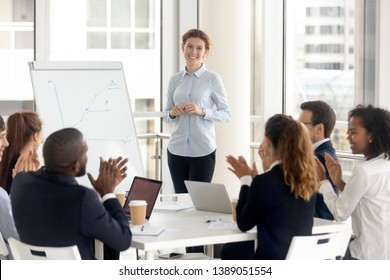 Multiethnic happy employees applaud thanking female speaker for successful flip chart presentation, excited diverse work group clap hands show gratitude to smiling woman coach seminar or training