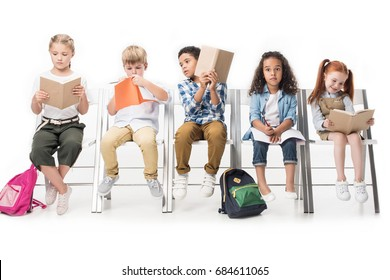 multiethnic kids reading books while sitting on chairs isolated on white