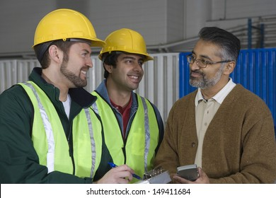 Multiethnic men discussing with clipboard and calculator in the factory
