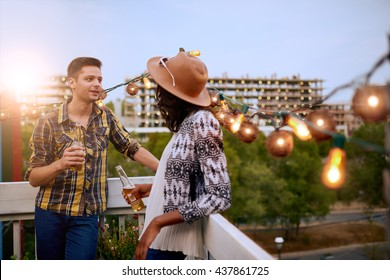 Multi-ethnic millenial couple flirting while having a drink on rooftop terrasse at sunset