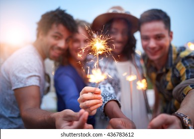 Multi-ethnic millenial group of friendsfolding sparklers on rooftop terrasse at sunset