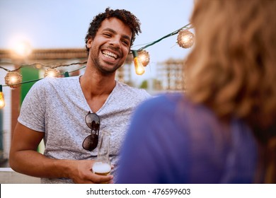 Multi-ethnic millennial couple flirting while having a drink on rooftop terrasse at sunset