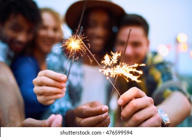 Multi-ethnic millennial group of friends folding sparklers on rooftop terrasse at sunset