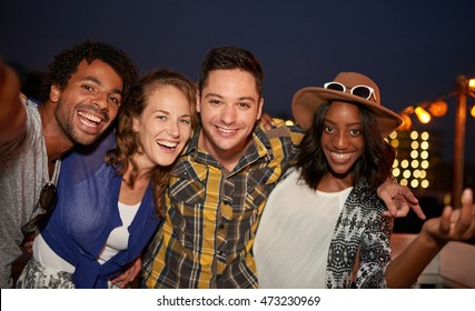 Multi-ethnic millennial group of friends taking selfie photo by mobile phone on rooftop terrace with a flash at night time