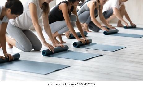 Multi-ethnic millennial people fold up grey exercise rubber carpets after work out session at sport club studio. Lifestyle and healthy life habit, weight loss, body and mind care, yoga class concept