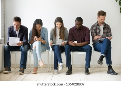 Multi-ethnic millennial people holding phones and resumes preparing for job interview, diverse vacancy applicants candidates wait in queue sitting in row, human resources, employment hiring concept