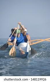 Multiethnic outrigger canoeing team paddling canoe in race