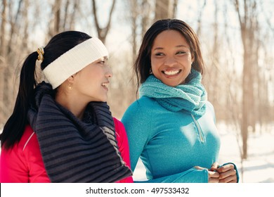 Multi-ethnic pair of female friends taking a break from jogging in the snow in winter
