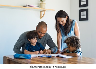 Multiethnic parents helping children with their homework at home. Young father and mother helping sons study at living room. Little boys completing their exercises with the help of dad and mom.