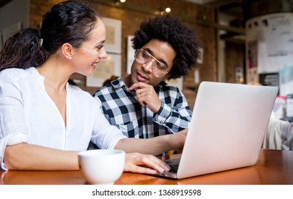 Multiethnic people meeting at cafe, advisor showing offer to client on laptop