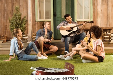 multiethnic people spending time together, man playing guitar while other friends listening