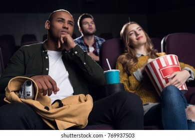 multiethnic people with video camera pirating in cinema