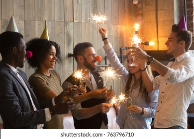 Multi-ethnic people wearing funny hats holding sparklers and glasses celebrating New year indoors, diverse friends congratulating each other drinking champagne at holiday eve party together