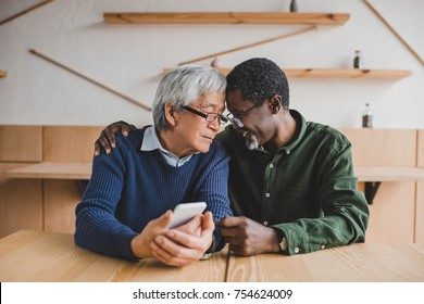 multiethnic senior men embracing while spending time together
