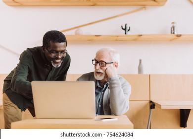 multiethnic senior men using laptop together