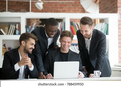 Multi-ethnic smiling businessmen in suits watching something funny on laptop in office together, diverse excited business team happy to see good news or work result profit growth on computer screen