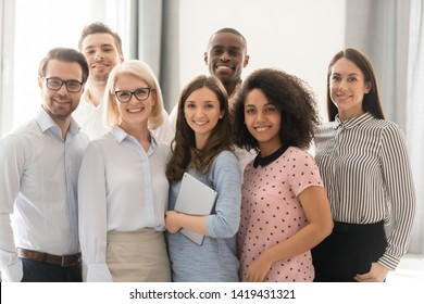 Multiethnic smiling businesspeople standing looking at camera making group photo in office together, happy diverse employees posing for picture with boss or team leader, showing unity and support