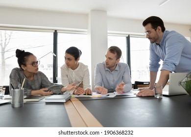 Multiethnic startup team gathering in office, discussing project plan and strategy. Millennial employees brainstorming and sharing ideas with group leader at corporate meeting. Teamwork concept