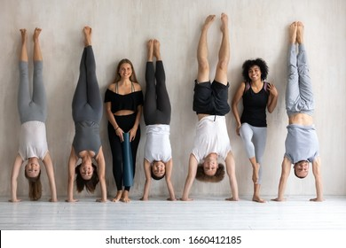 Multiethnic strong sportive people in sportswear posing standing near wall, diverse sportsmen sportswomen performing handstand smile look at camera, yoga work out finish, wellness, having fun concept