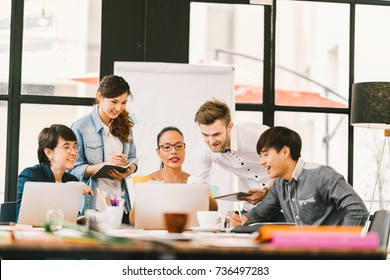 Multiethnic team busy discussion using laptop, digital tablet. Coworker partnership, college student meeting. Small business casual office, freelance designer job, or online marketing analysis concept