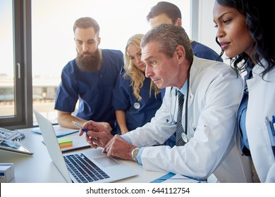 Multiethnic team of doctors looking at laptop during meeting in hospital.