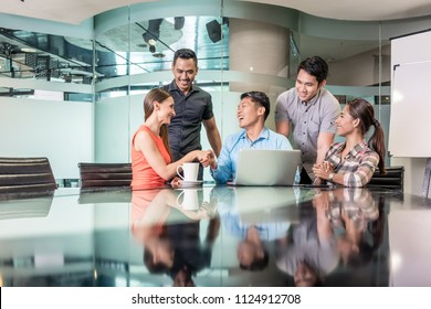 Multi-ethnic team of five dedicated employees sitting in front of a laptop while working together at an innovative business project in a modern office