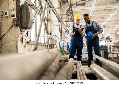 Multi-ethnic team of inspectors wearing overalls and hardhats standing at spacious production department of modern plant while making inspection, one of them writing something down
