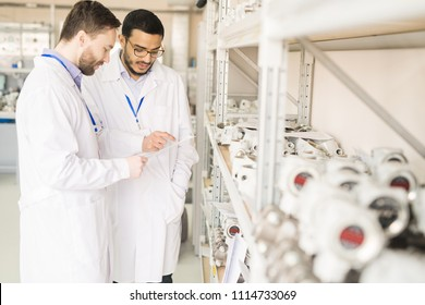Multi-ethnic team of quality control engineers wearing lab coats studying document while standing at spacious warehouse of pressure transducer factory and carrying out inspection