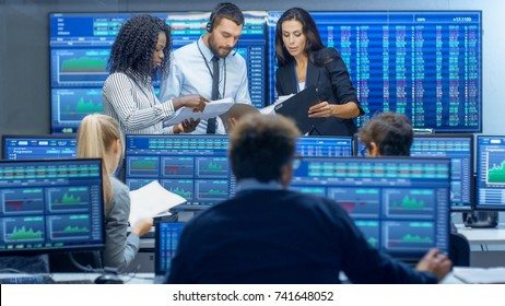Multi-Ethnic Team of Traders is Busy Working at the Stock Exchange Office. Dealers and Brokers Buy and Sell Stocks on the Market. Monitors Display Relevant Infographics, Data and Numbers.