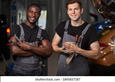 multiethnic team of two auto mechanic males at work place, successful work of diverse workers in uniform, they are posing at camera